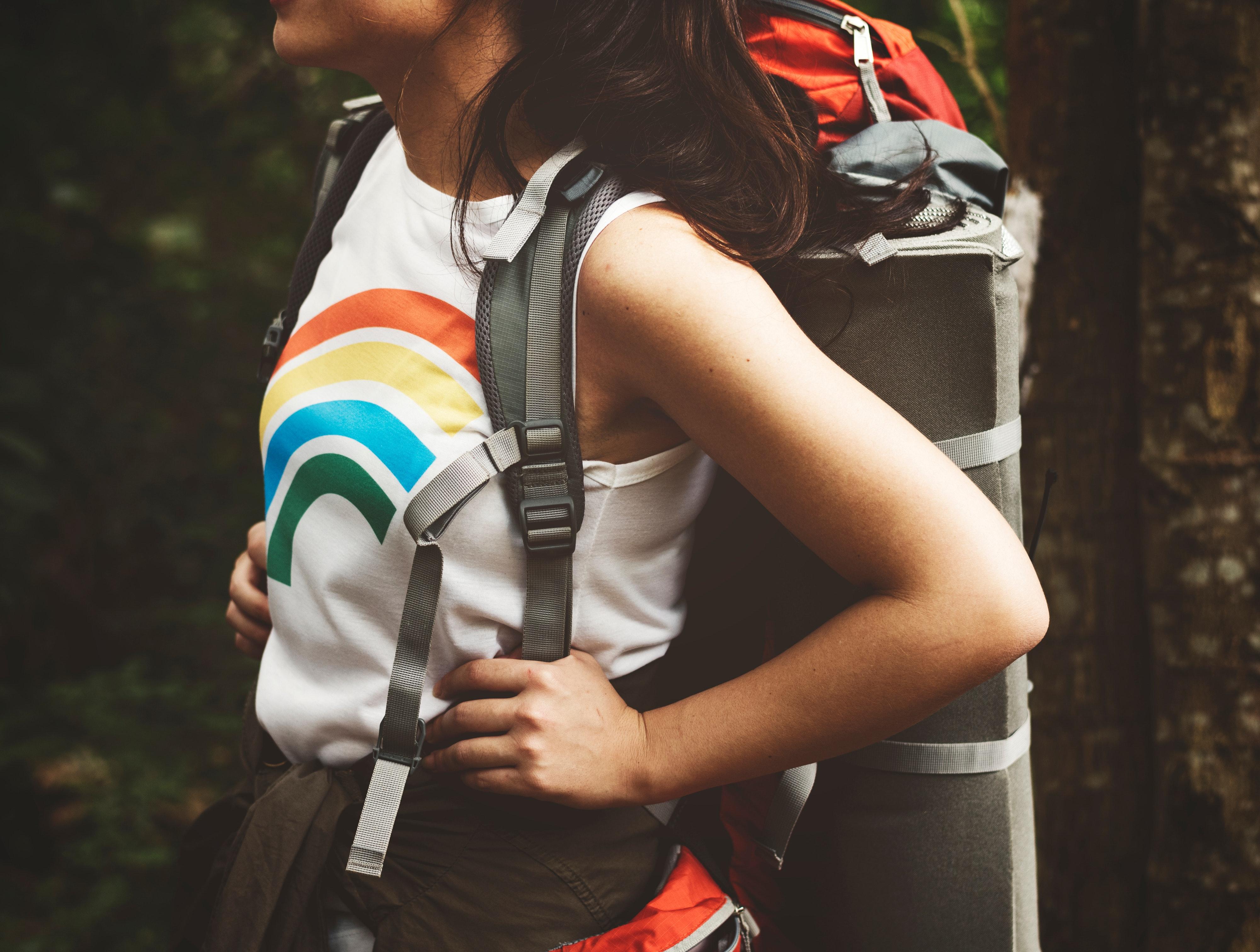 Imagen que contiene mochila, colores, naturaleza, chica